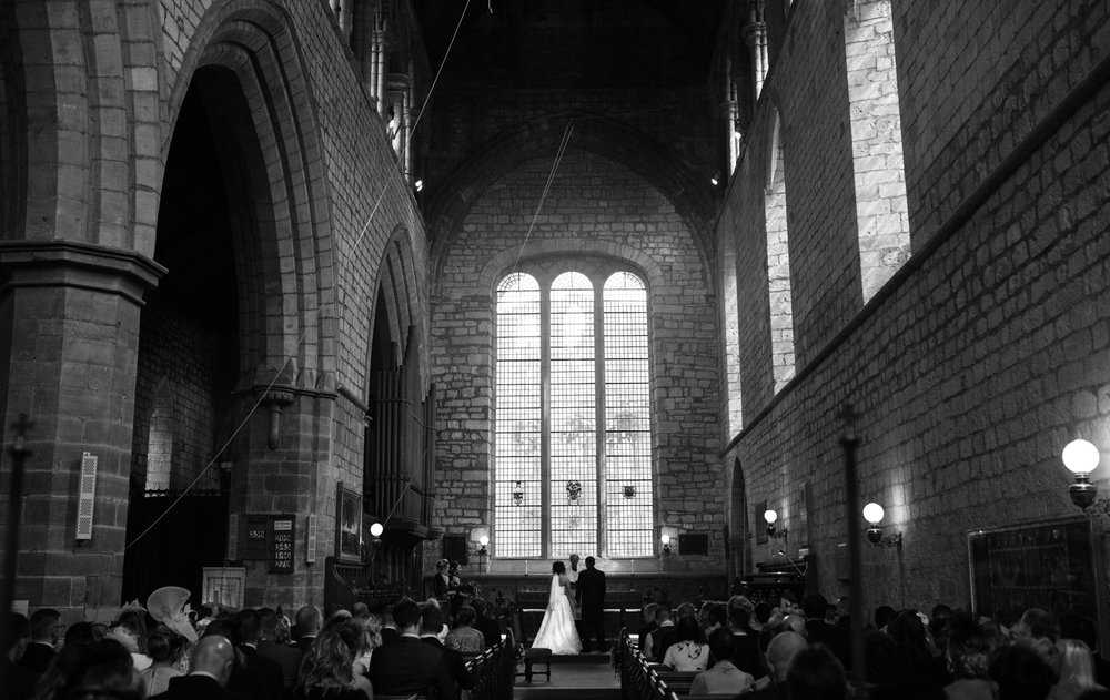 black and white image of the bride and groom from the very back of the priory