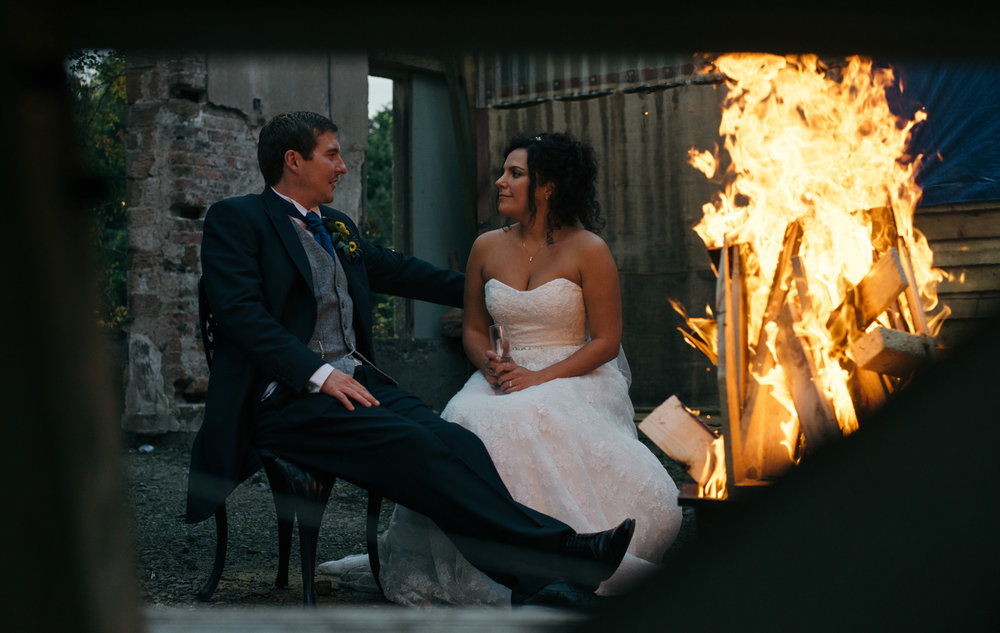 Bride and groom sitting by the fire