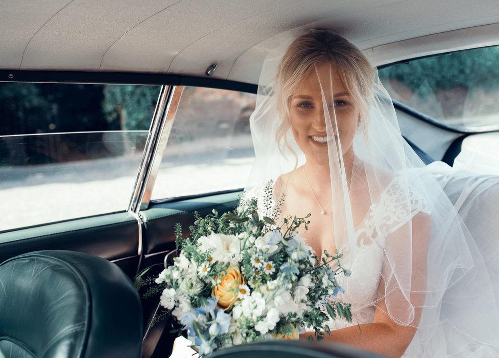 The bride sitting in the back of the Aston Martin as she arrives at the church