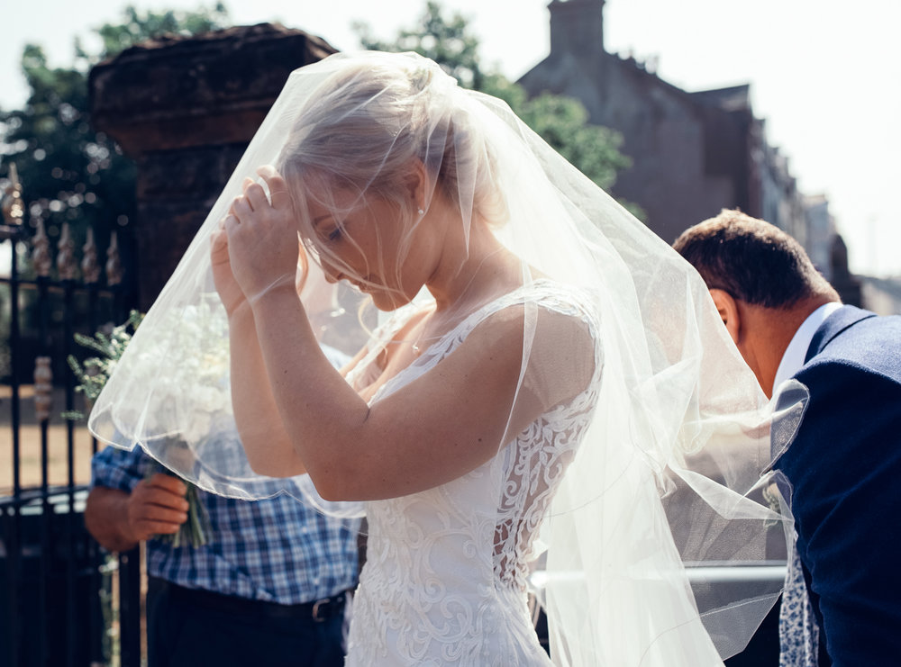 The bride adjusting her veil before going into church