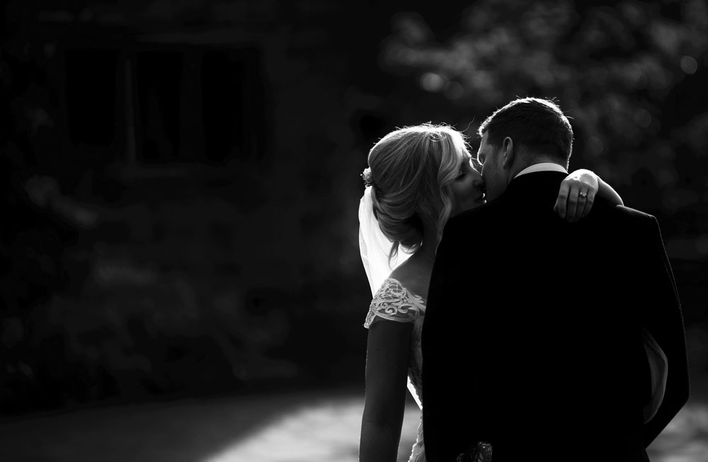 Black and white photo of the bride and groom kissing low key image