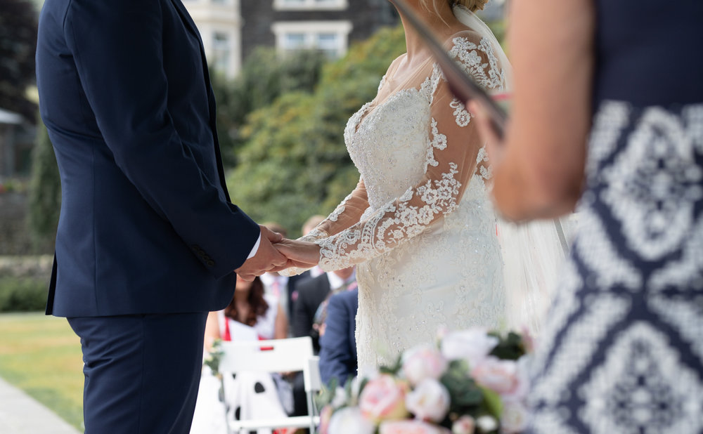 The bride and groom holding hands during the wedding ceremony