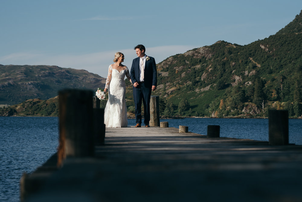 The bride and groom walking down the jetty