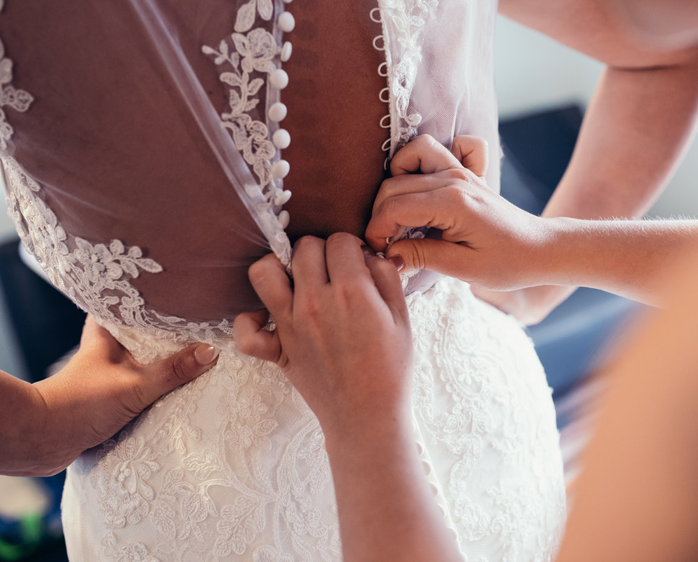 The bride being buttoned into her amazing wedding dress
