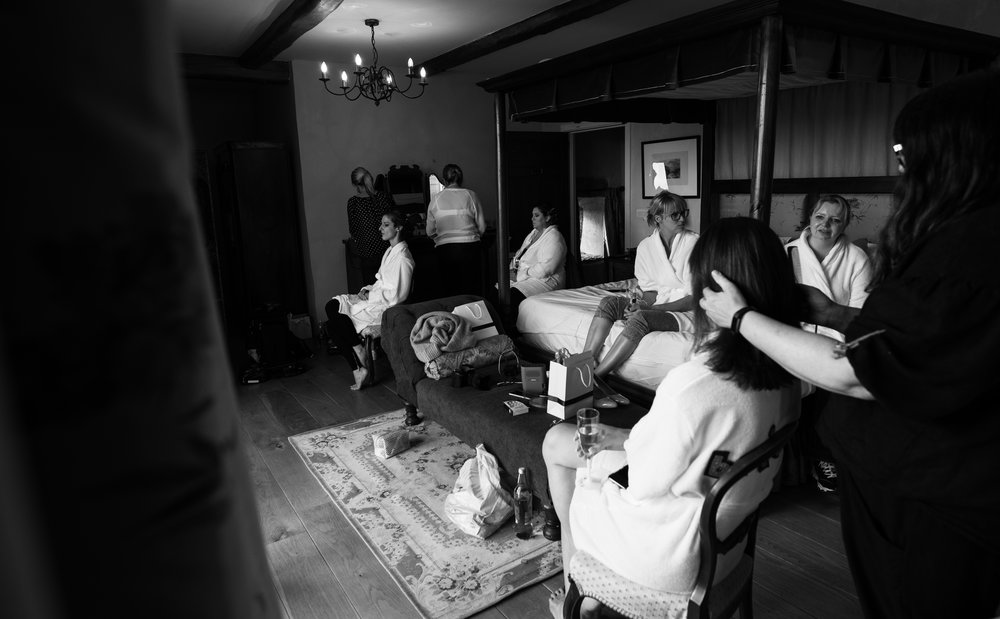 A wide angle black and white photo of the bride and bridesmaids getting ready