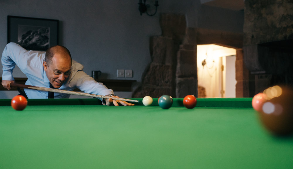One of the male guests enjoying a game of snooker before the wedding ceremony