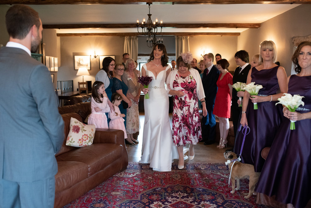 The bride being walked down the aisle by her mum