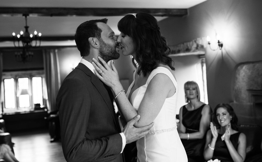 Black and white image of the bride and grooms first kiss as a married couple
