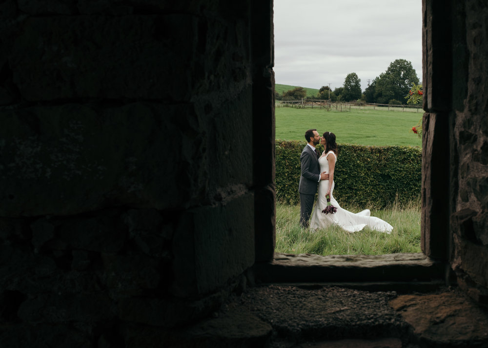 The bride and groom kissing in the meadow taken through an open window