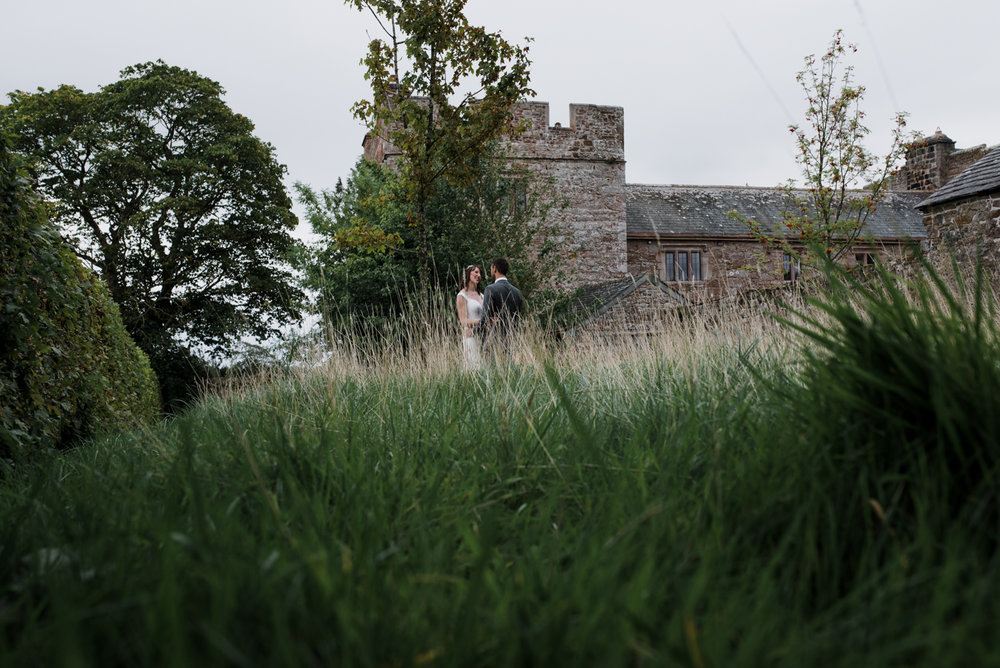 The bride and groom standing in the meadow with Blencowe Hall in the background