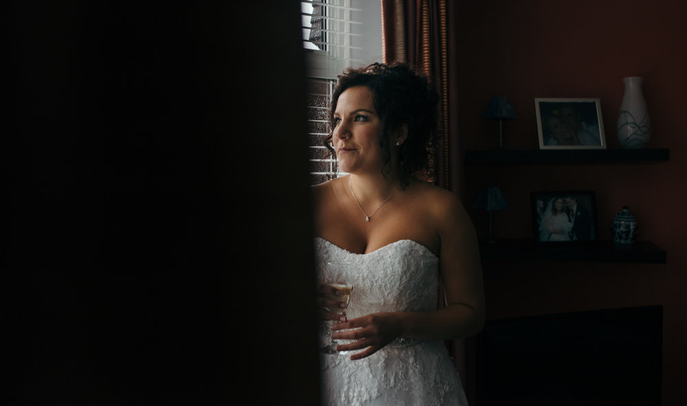 The bride looking out of the living room window waiting for the cars to arrive