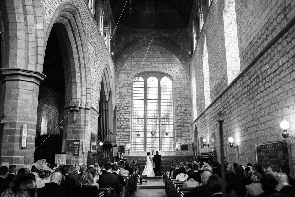 A wide angle black and white image taken from the very back of the church looking back towards the alter during preyers