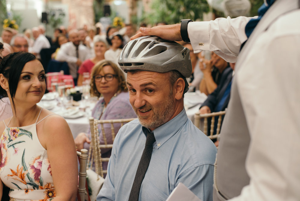 One of the male guests is presented with a cycle helmet during the speeches private joke