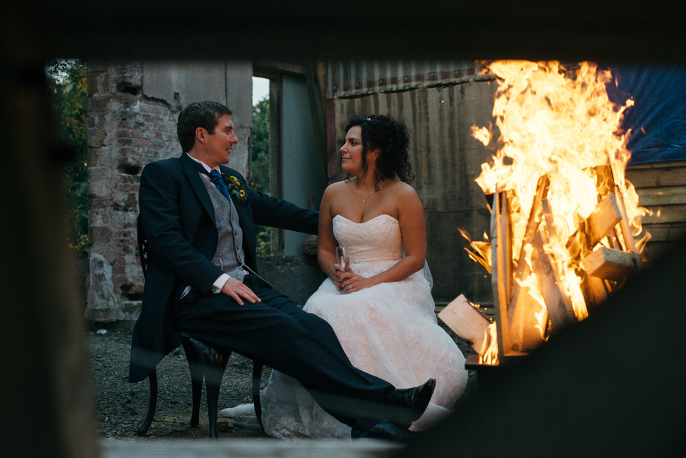 The bride and groom sitting chatting by one of the outdoor fire pits