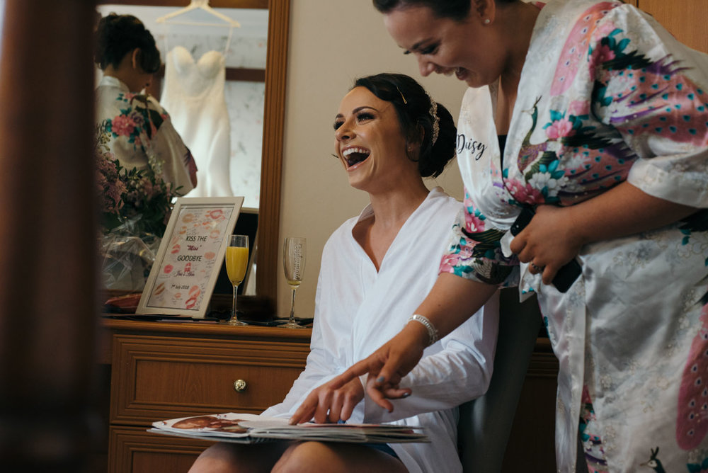 The bride Jessica having a good laugh at some of the photos in an album given to her by the bridesmaids