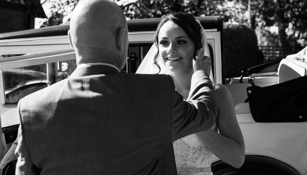 The brides father gives the bride a hug before going into the church