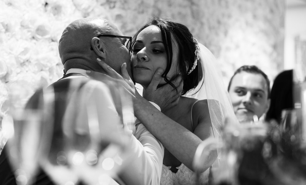 The bride giving her father a kiss during the speeches