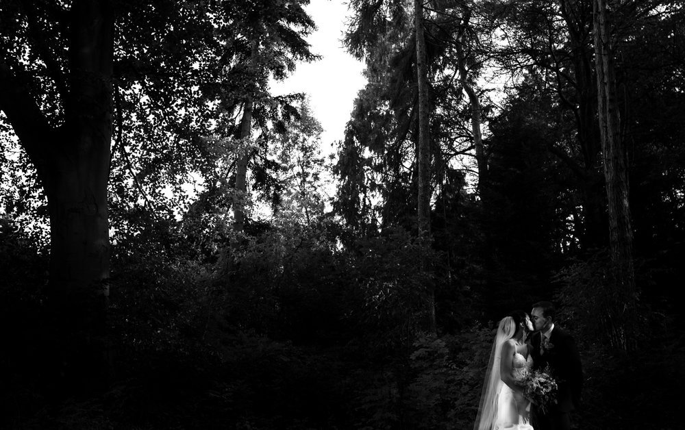The bride and groom kissing in this black and white image in the woods