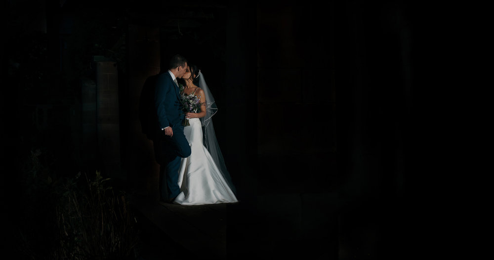 A dark and moody photograph of the bride and groom taken at night time