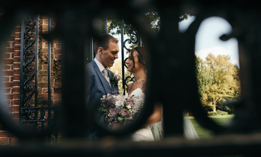 An image of the happy couple taken through the railings of the wrought iron gates