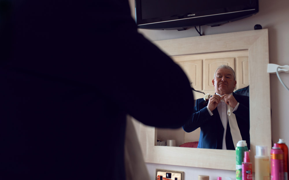 Image if the brides father adjusting his tie in the mirror