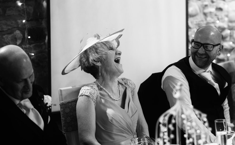 The mother of the groom laughing during the speeches