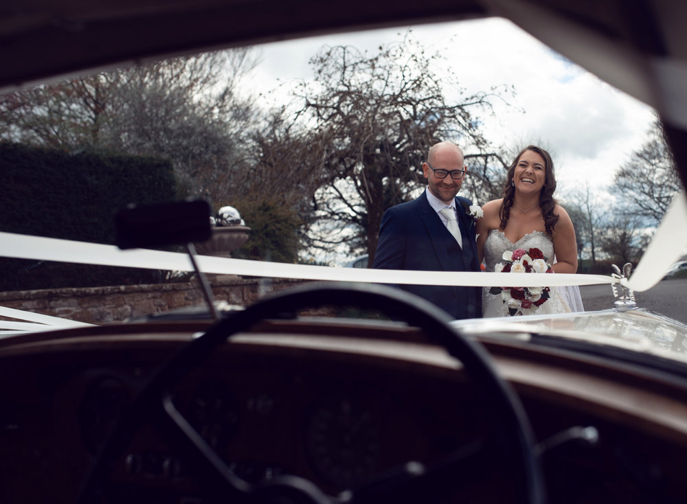 Photo of the bride and groom from inside the car