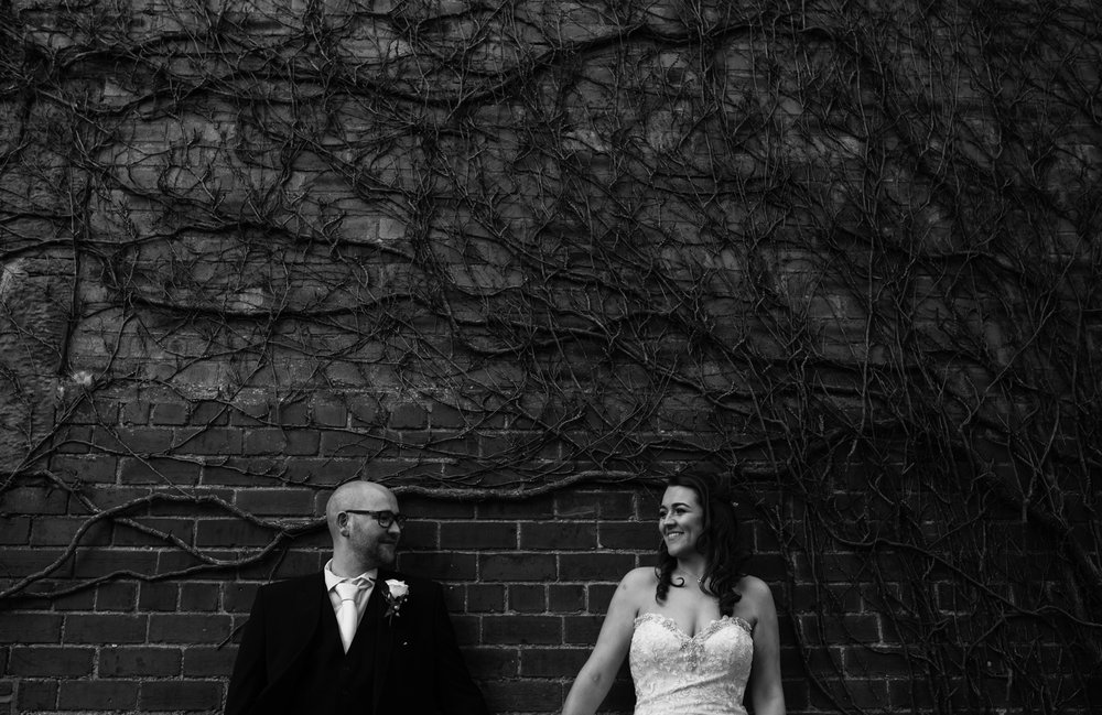 A black and white photo of the bride and groom standing in front of a wall during couples portraits