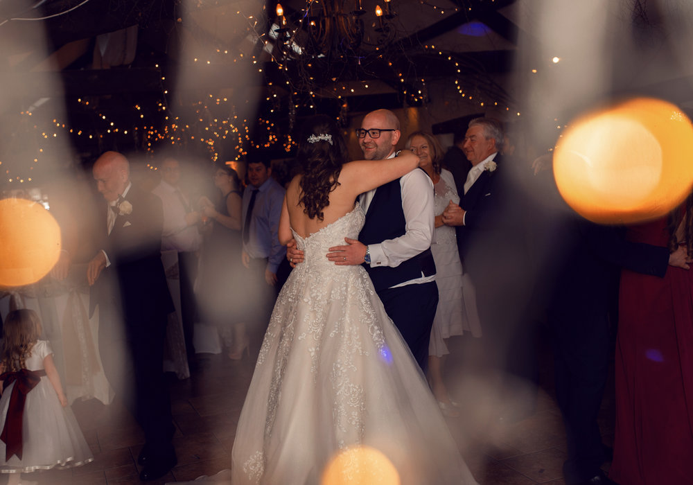A photo of the bride and groom during the first dance taken though fairy lights
