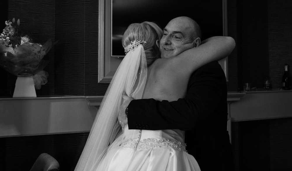 Black and white photo of the bride and her father having a hug when he sees her for the first time