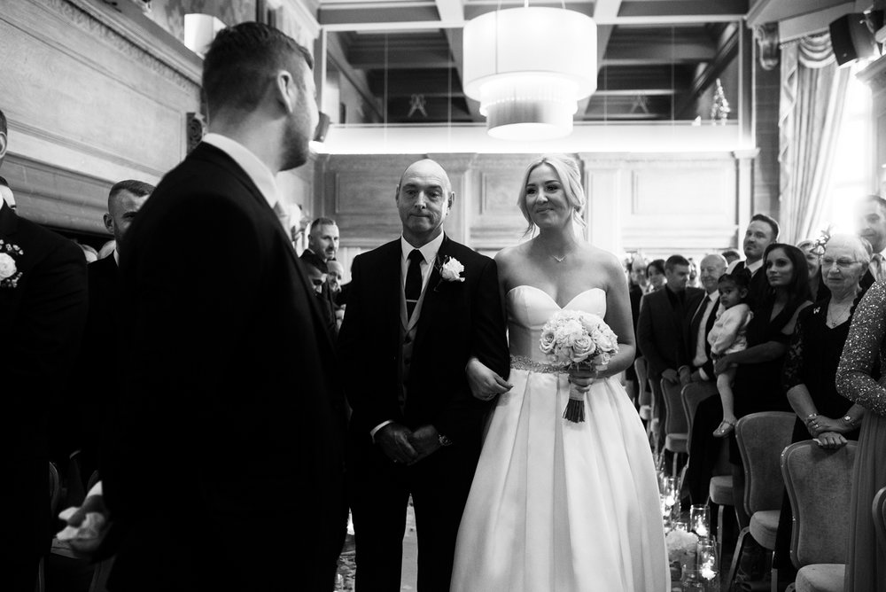 A black and white photo of the bride and her dad when they reach the end of the aisle