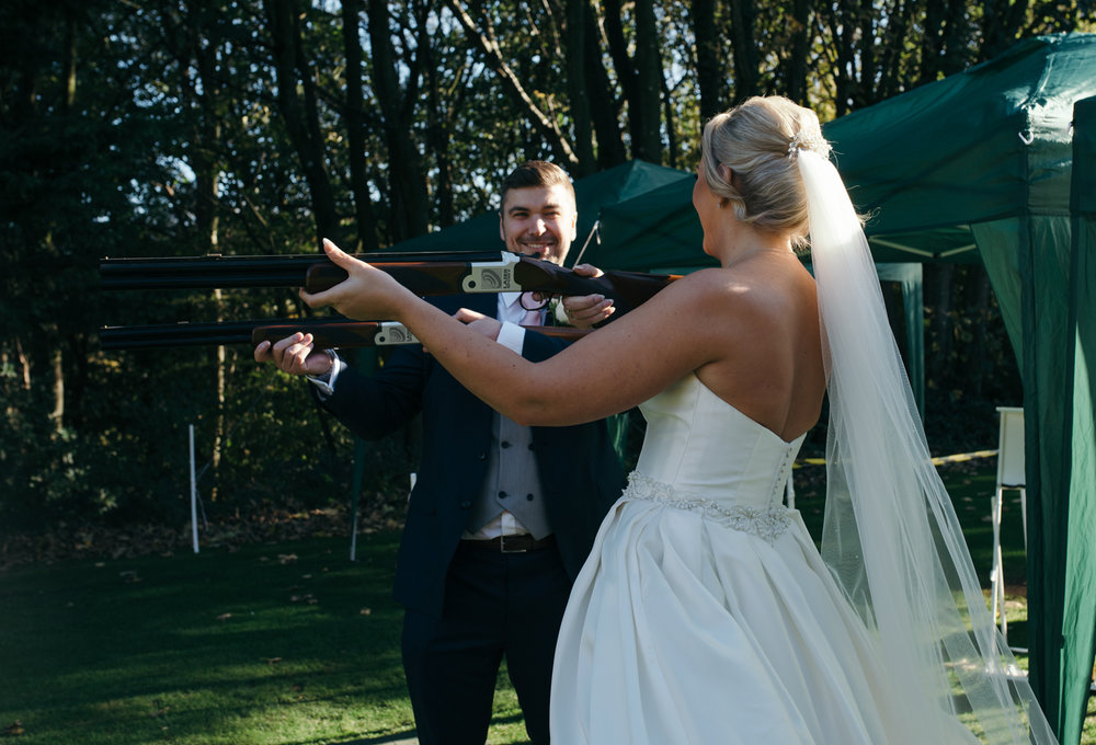 The bride and the groom both having a try at laser clay pigeon shooting
