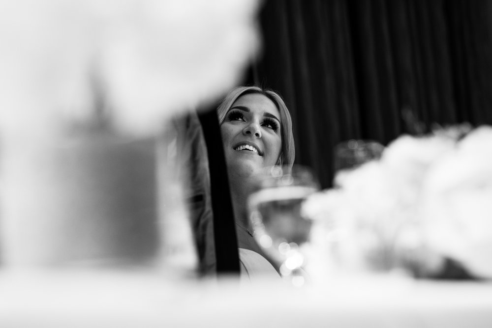 Black and white photo of the bride looking up at the groom during his speech