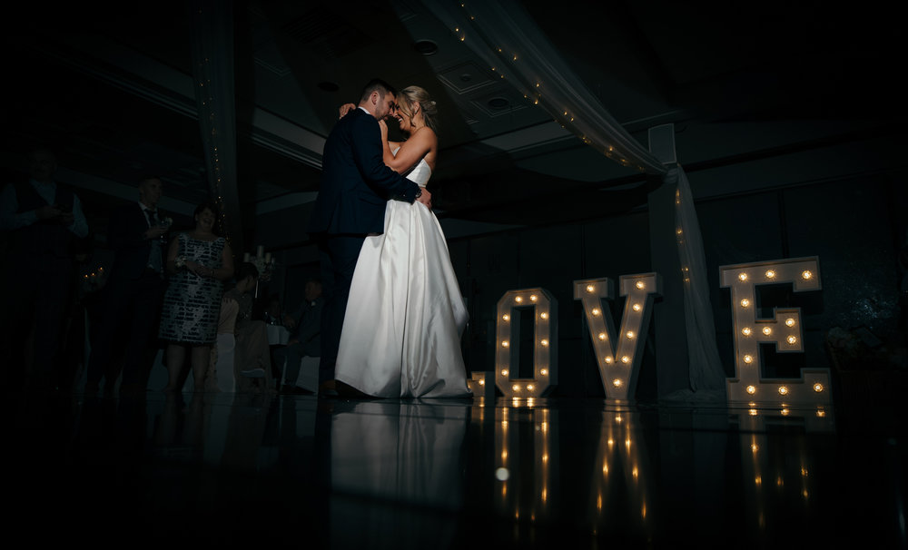 The bride and groom during their first dance featuring the large light up love letters