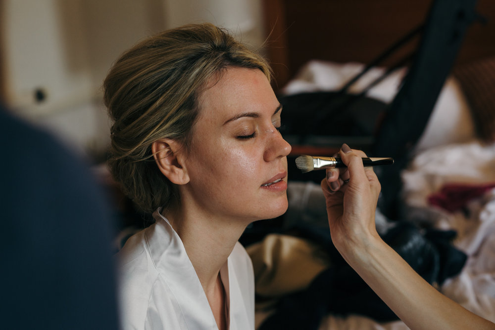 The bride having her makeup applied during durning bridal preparations