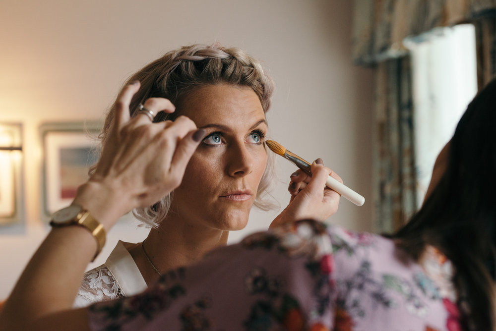 A bridesmaid having her eye makeup done