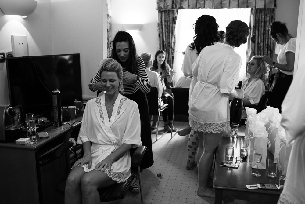 A black and white wide angle photo of the whole group during bridal preparations