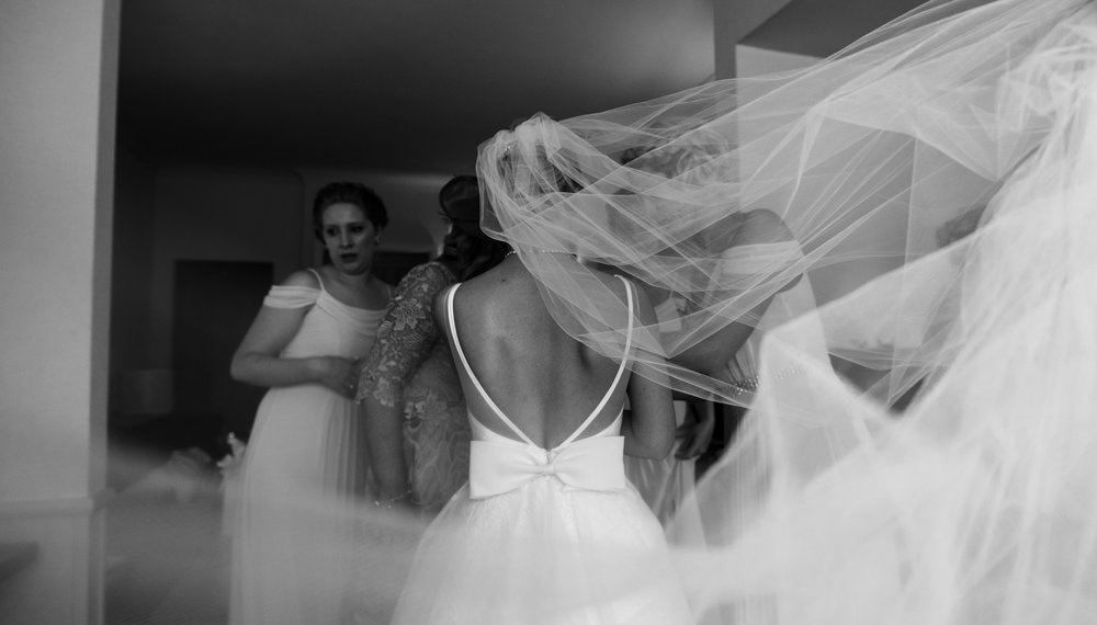 A black and white photo of the back of the brides dress with the veil flowing behind her