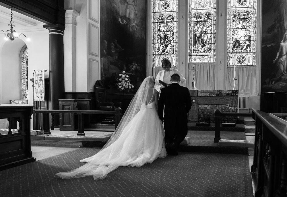 A black and white photo of the bride and groom kneeling before the alter