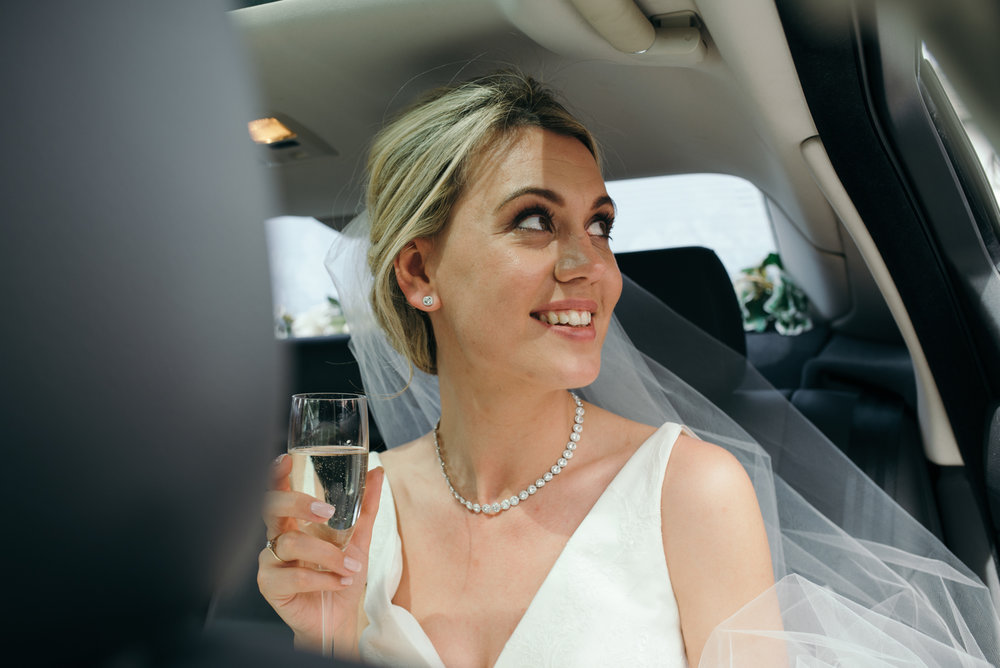 The bride enjoying a glass of bubbly as they arrive at Low Wood Bay Hotel
