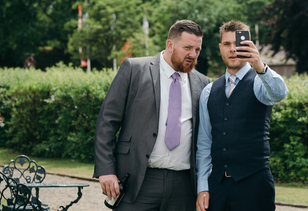 To male wedding guests caught taking a selfie together