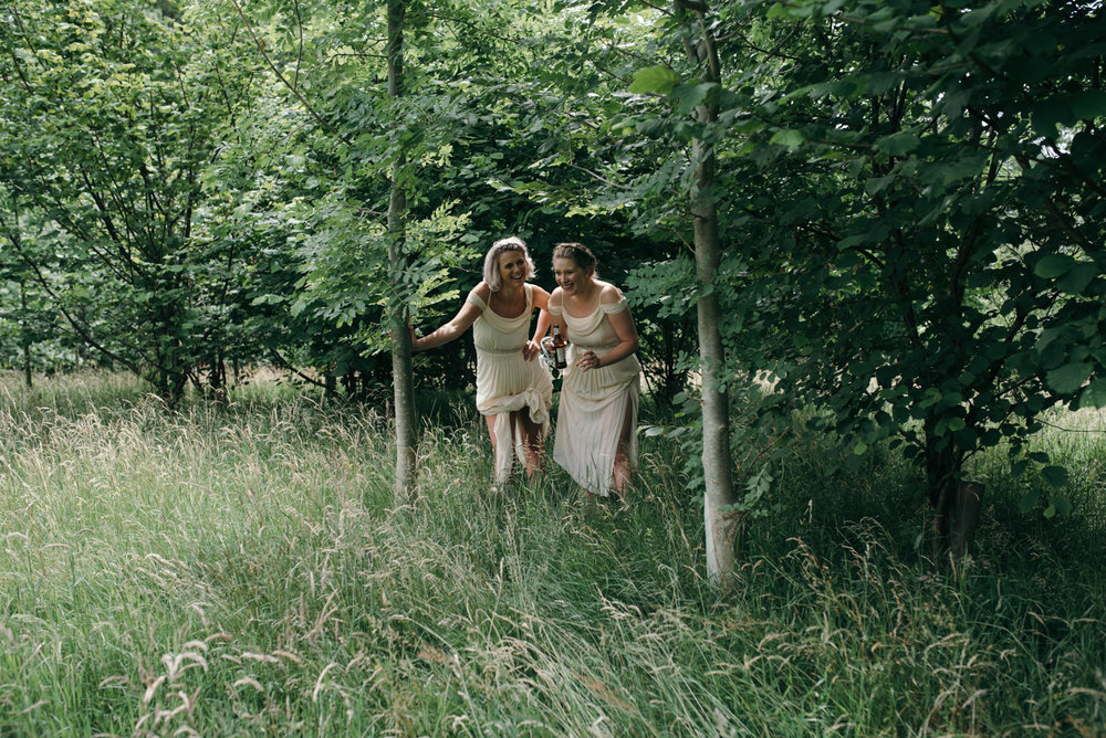 Two bridesmaids hiding in the bushes laughing during the couples portrait photo shoot