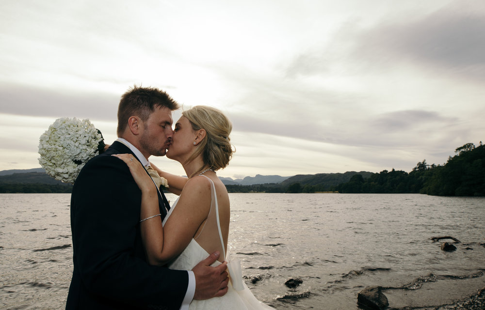 A sunset portrait of the bride and groom taken down by the boat jetty on Windermere