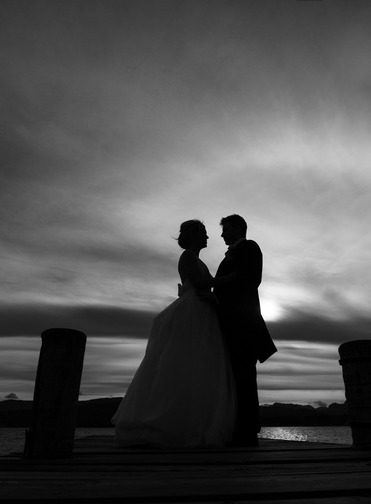 A black and white silhouette photo of the bride and groom standing on the jetty on the shoreline