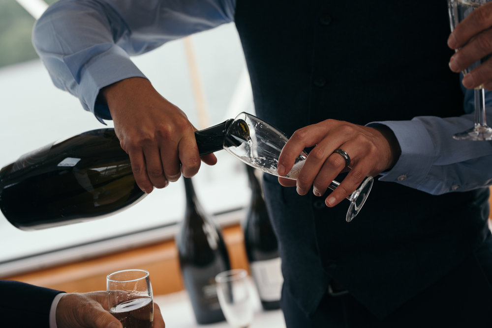 Photo of a guest topping up the glasses with Prosecco during the lake cruise
