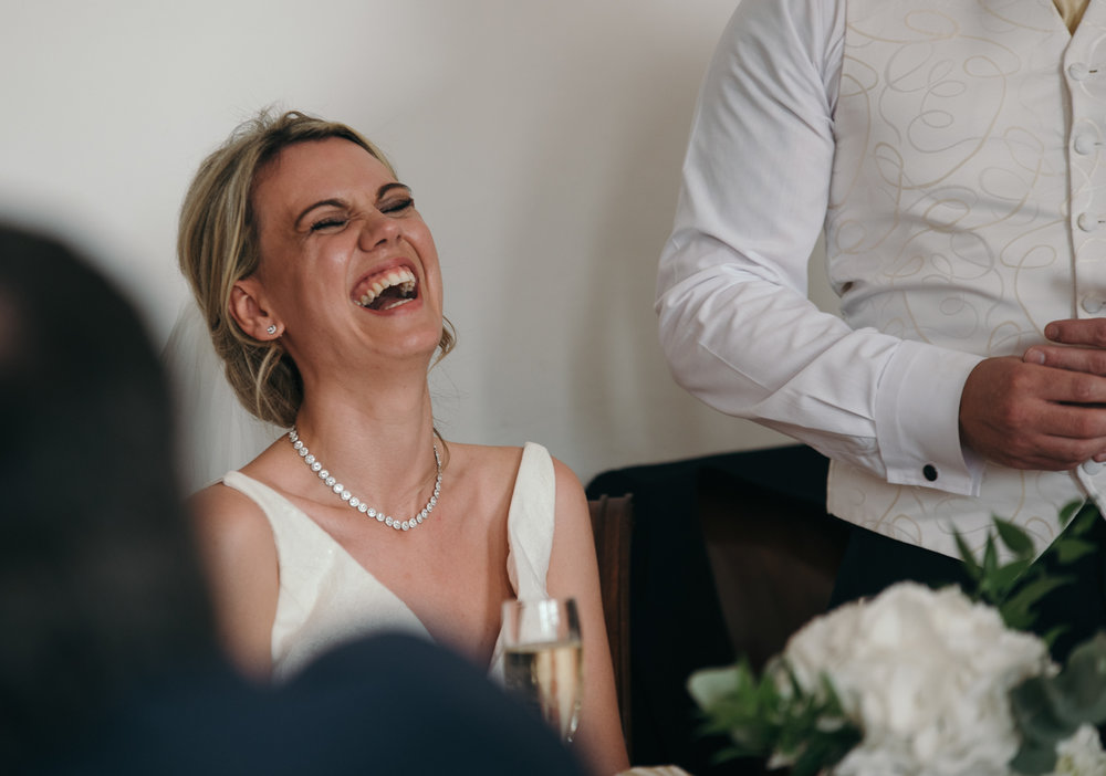 The bride laughing during the grooms speech