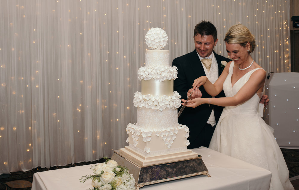 The bride and groom giggling whilst cutting the wedding cake