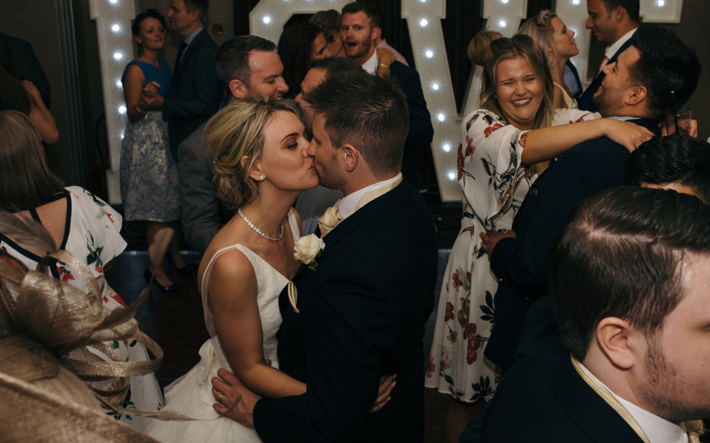 The bride and groom having a kiss on the dance floor whilst everything else is madness around them