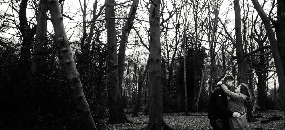 Pre shoot A black and white photo of a couple in the woods hugging