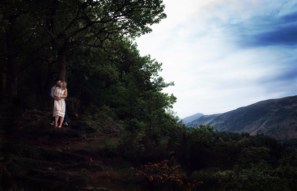 Pre shoot - A wide angle distant photo of a couple standing in the trees overlooking Derwent Water in the Lake District